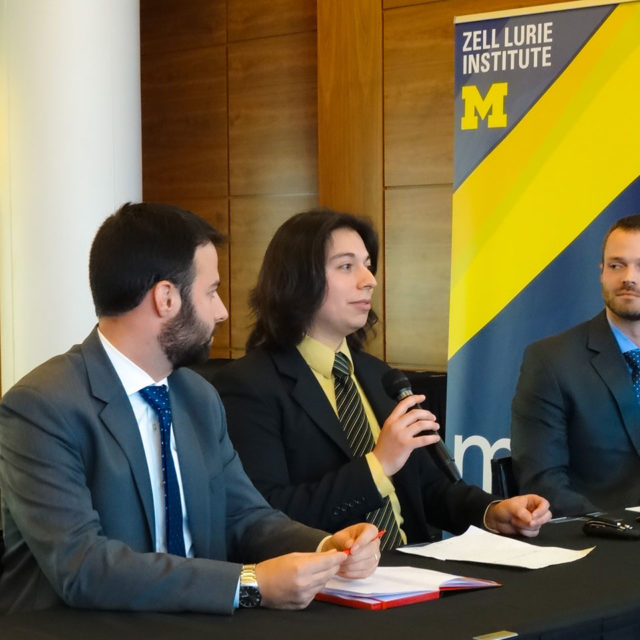 Ramses Alcaide, center, pitches at the Zell Lurie Institute's Michigan Business Challenge in April. Michael Thompson, right, Neurable business development manager, and Max Jacobson, left, an MBA student, listen.